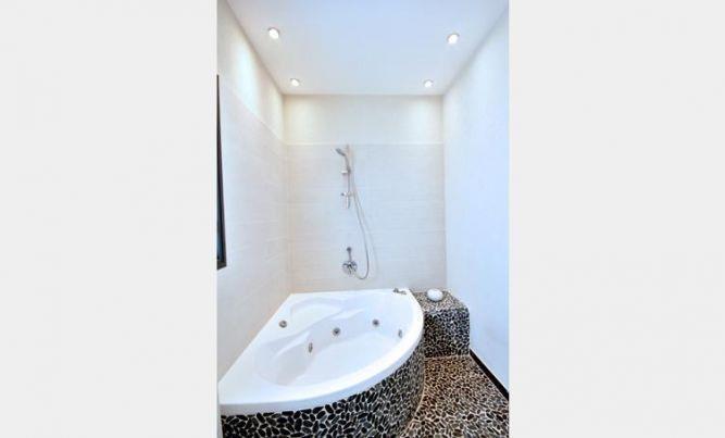 חדר אמבט מעוצב בדירתו של ליאור סושרד בדגש על פסיפס אבנים שחורים  בתכנון ועיצוב של קרן רוזנר