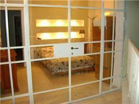 מבט אל חדר השינה מהמרפסת הצמודה -דגש על אור טבעי ותאורה רכה. עיצוב של חיה ברק