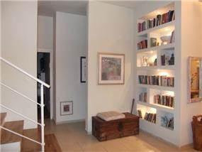 ספריה הממוקמת בגב קיר הכניסה לבית, בעיצוב חיה ברק ומירב אייל הרפז