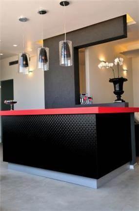 דלפק הכניסה במכון יופי בנמל ת''א, שילוב של אדום ושחור בסגנון מודרני. עיצוב: חיה ברק - סטודיו Hb