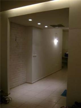 יצירת מבואת כניסה מהנמכת תקרה עם תאורה נסתרת וקיר לבנים כשהצד האחורי משמש כספריה. עיצוב של חיה ברק