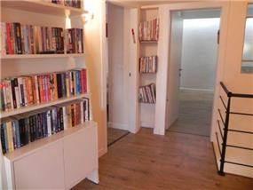 מבואה בבית הכוללת פתרונות אחסון לספרים בתכנון ועיצוב של אופן ספייס