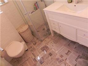 מבט אל חדר אמבטיה המרוצף בדוגמת גזרי עיתונים. עיצוב: אופן ספייס