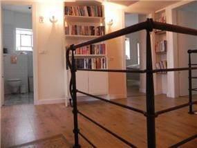 מבט אל מבואת החדרים בדגש על רצפת הפרקט והתאורה. תכנון ועיצוב של אופן ספייס