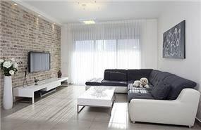 סלון דירה מעוצב בקווים קלאסיים בשילוב קיר בריקים. עיצוב: יעל אפרתי תכנון ועיצוב פנים