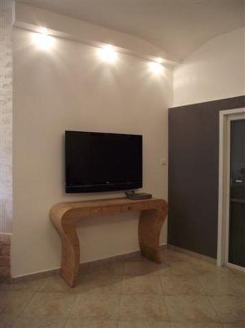 סלון מעוצב עם תאורה שקועת קיר ושולחן עץ ייחודי, עיצוב ותכנון של סטודיו פרטים