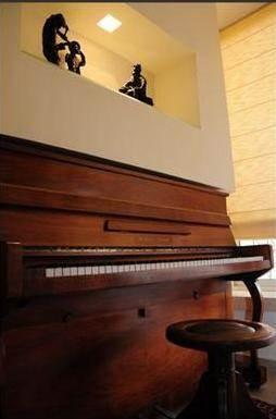פסנתר בחלל עם נישת גבס מעוצבת ותאורה תואמת בתכנון ועיצוב של a&e design