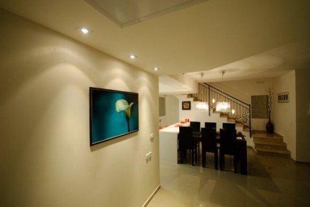 מבט אל פינת האוכל המעוצבת בדגש על תאורת הקיר בתכנון ועיצוב של שרי בר נע גבעון
