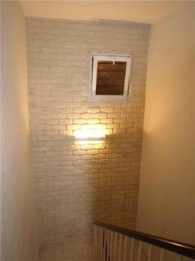 מבואת כניסה עם קיר דמוי בריקים עם תאורה מעוצבת של שרי בר נע גבעון