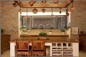 מטבח כפרי המשלב קיר בריקים, אי עבודה וישיבה והרבה עץ, בעיצוב ארכידרום אדריכלים