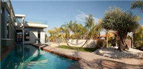 חצר מעוצבת הכוללת בריכה ושטח צמחיה בעיצוב ארכידרום אדריכלים