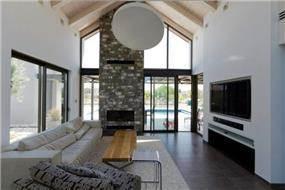 קיר בריקים גדול ותקרה עם קורות חשופות בסלון, עיצוב: Saab Architects
