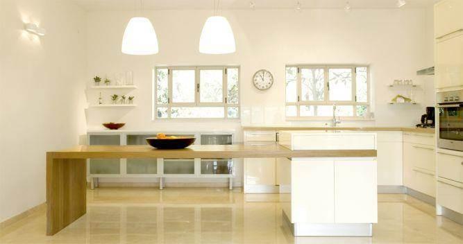 מטבח בהיר בעיצוב מודרני הכולל אי עבודה וישיבה גדול במרכז. עיצוב: Saab Architects