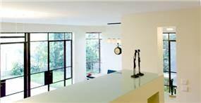 מבט מקיף אל פנים הבית. חלל בהיר עם דלתות יציאה לחצר עם פרזול כהה ודומיננטי. עיצוב: Saab Architects