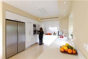 מטבח לבן בשילוב קיר הצבוע בגווני מוקה,  עיצוב Saab Architects