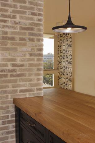 """מבט מהמטבח אל קיר הבריקים הצמוד לו, בדירה למכירה בת""""א. עיצוב: טלי סטוף"""