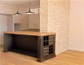 מבט אל המטבח המעוצב בקו כפרי וחם ונושק לקיר בריקים, בדירה למכירה בתל אביב. עיצוב: טלי סטוף