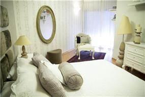 מבט צד לחדר שינה מעוצב בקו נקי תוך כדי הקפדה על הפריטים הקטנים בסגנון וינטאג' בעיצוב ותכנון של ג'ני דיין