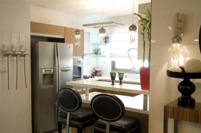 מבט כולל אל מטבח מעוצב במראה מודרני והקפדה על אביזרי  ההוםסטיילינג המשלימים