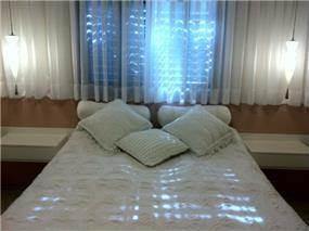 חדר שינה הורים בקו נקי נעים בגוונים רכים ועדינים.