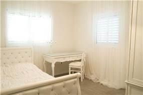 חדר שינה במראה קלאסי על טהרת גווני הלבן בעיצוב ותכנון של ג'ני הום סטיילינג