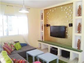 """סלון עם ספסל בנוי ונישות לתצוגה וספה משודרגת. עיצוב מודרני ע""""י MikMik Design - מיקה אלטר."""