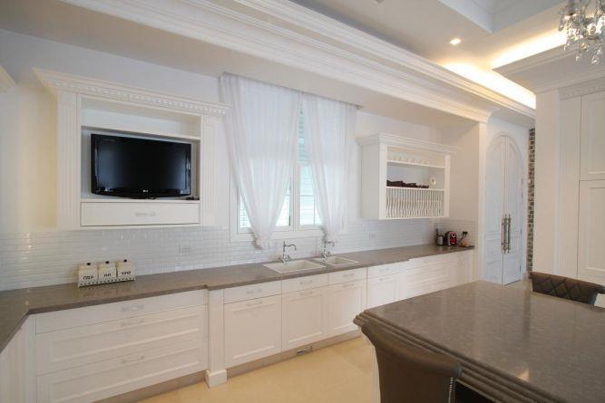 עיצוב מטבח מרשים בגווני לבן וחום, הכולל גם נישה לטלויזיה. HM מושיק חדידה-אדריכלות ועיצוב פנים
