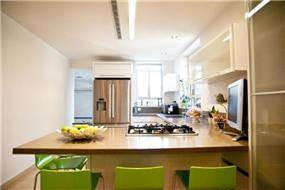מבט אל מטבח המעוצב בשילוב בר עם כסאות ירוקים. בעיצוב ליהי שמאי