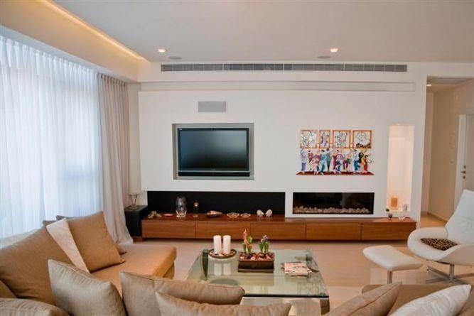 מבט אל סלון בעיצוב נקי ואלגנטי קיר טלוויזיה מעוצב משולב בקמין. בעיצוב- ליהי שמאי