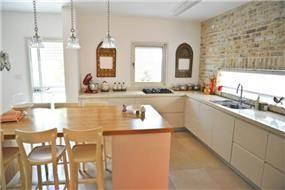 מבט אל מטבח מודרני המעוצב בקווים נקיים משולב בבריקים מפירוק ובבוצ'ר עץ. בעיצוב- ליהי שמאי