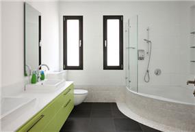 חדר רחצה ילדים עם ארון בגוון ירוק ואמבטיה פינתית לבנה, טלי מאיר פיק