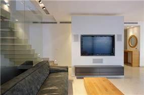 מבט על קיר טלוזיה שמשמש הפרדה בין חלל כניסה לסלון, טלי מאיר פיק