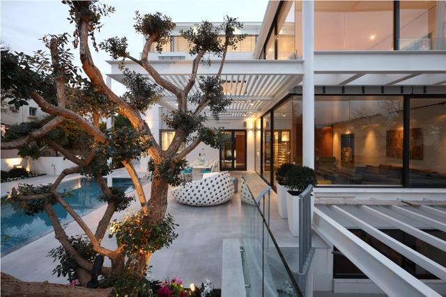 מבט צד אל בית יוקרתי עם בריכה ושפע פתחים לאור טבעי בתכנון מרק טופילסקי