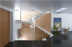 מדרגות פלדה ואבן מרחפות לצד פינת אוכל מודרנית. עיצוב: אדריכל מרק טופילסקי