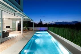 בריכה לאורך בית עם תאורה בסגנון מודרני ודק עץ במרפסת בתכנון מרק טופליסקי