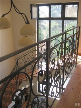 אלמנט מדרגות מעוצב בחלל כפול הפתוח לנוף כפרי ירוק.