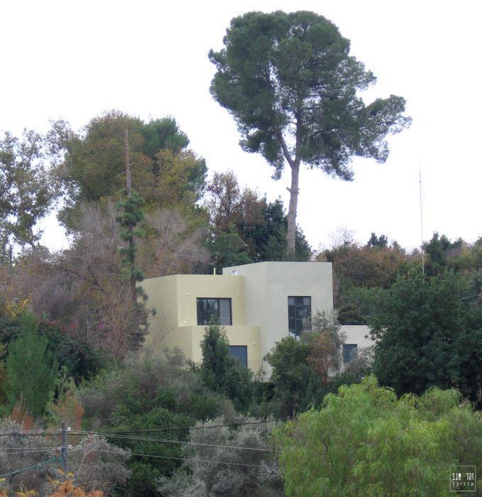 בית פרטי בסגנון מודרני רך, טובל בסביבה ירוקה.