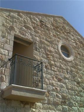 חזית בית פרטי בסגנון מודרני המשלב איזכורים סיגנוניים טמפלרים.