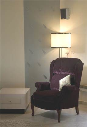 פינה נינוחה בסלון. קיר דקורטיבי משולב בעלי כסף ותאורה תואמת