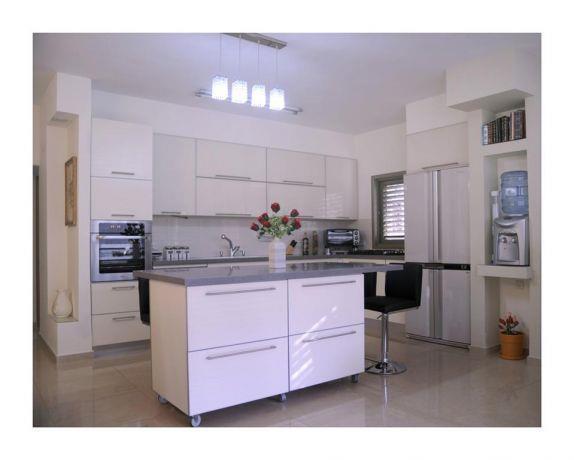 מטבח בעיצוב נקי על טהרת הצבע הלבן עם שלל מקומות אחסון ואי תואם