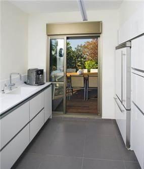 מטבח בחלוקה מקבילה על מנת לאפשר יציאה נוחה לחצר, עיצוב לילך לויט