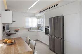 מטבח מודרני בגימור אפוקסי לבן ושילוב פרטי גמר משלימים. עיצוב: יוסי שאול YS-DESIGN