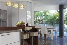 מבט מהמטבח לעבר פינת האוכל והמרפסת, המעוצבים כולם בסגנון מודרני. עיצוב פנים: יוסי שאול.YS-DESIGN