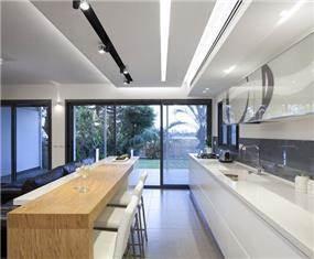 מטבח מודרני,מוקפד ונקי, בשילוב בר ותאורה.עיצוב: יוסי שאול YS-DESIGN