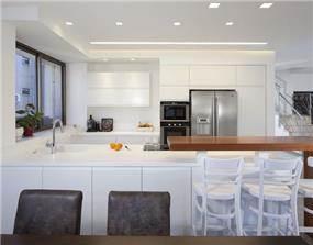 מטבח מודרני, מוקפד ונקי, בשילוב בר ישיבה וגופי תאורה. עיצוב של יוסי שאול YS-DESIGN