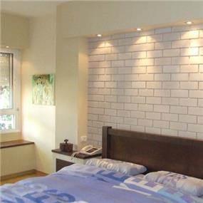 קיר בריקים לבן בגב המיטה, עיצוב ורד פולקמן