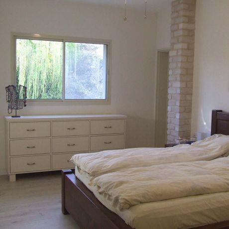 שני עמודי לבני סיליקט תוחמים את המיטה בחדר השינה, עיצוב ורד פולקמן