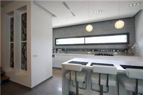 מטבח מודרני עם פינת אכילה בצבעים בהירים בתוך בית בכרכור. עיצוב:CG DESIGN - כרמית גורש עיצוב ואדריכלות פנים