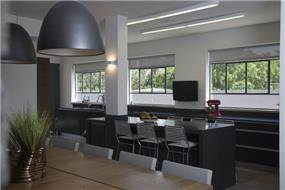 מטבח ארוך עם חלונות גדולים ואי מרכזי. עיצוב של ענבל ברקוביץ