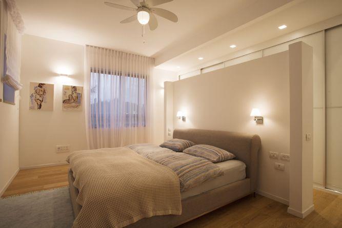 חדר שינה הכולל מחיצת גבס גבוהה שיוצרת הפרדה מהארון. עיצוב של ענבל ברקוביץ